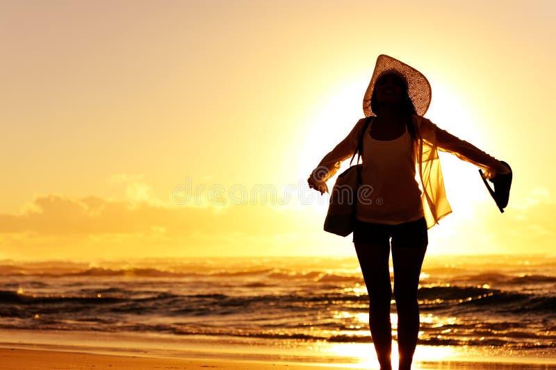 Mujer de la puesta del sol de la playa imagenes de archivo