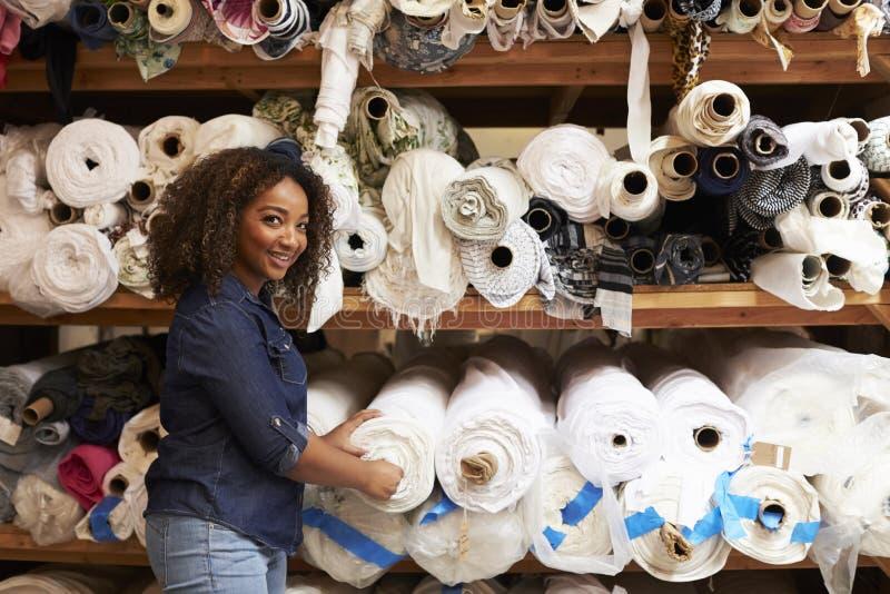 Mujer de la raza mixta que selecciona las telas que miran a la cámara imagen de archivo libre de regalías