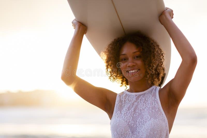 Mujer de la raza mixta que sostiene una tabla hawaiana en la puesta del sol imagen de archivo libre de regalías