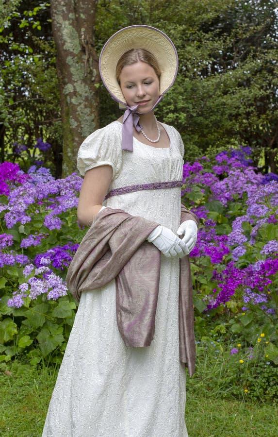 Mujer de la regencia en un vestido, un mantón de Paisley y un capo poner crema foto de archivo libre de regalías