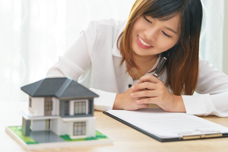 Mujer de la sonrisa que parece en casa y que consigue lista para firmar el contrato f imágenes de archivo libres de regalías