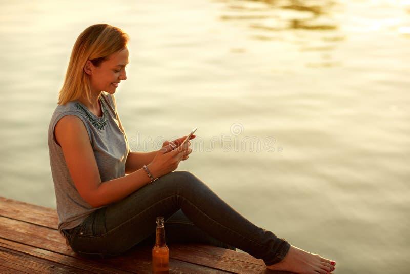 Mujer de la sonrisa que se sienta en muelle y que mira celphone fotos de archivo