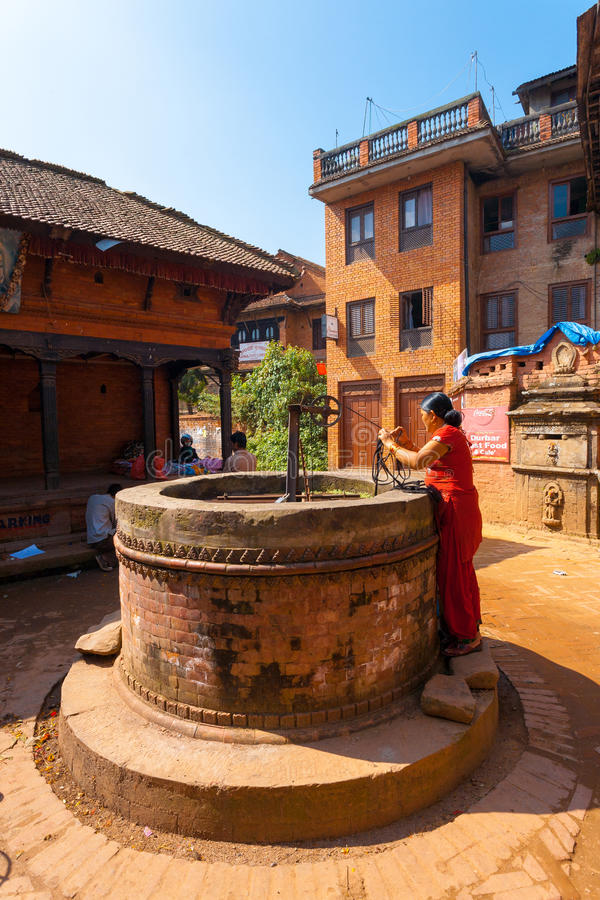 Mujer de la vida del pueblo de Nepal que tira del agua bien foto de archivo