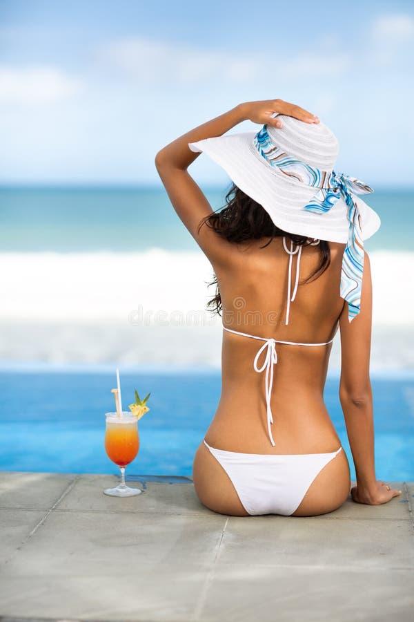 Mujer de la vista posterior del sombrero de la playa con el cóctel imagen de archivo