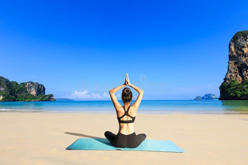 Mujer de la yoga en costa de mar imagenes de archivo