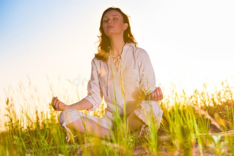 Mujer de la yoga en hierba verde imagen de archivo