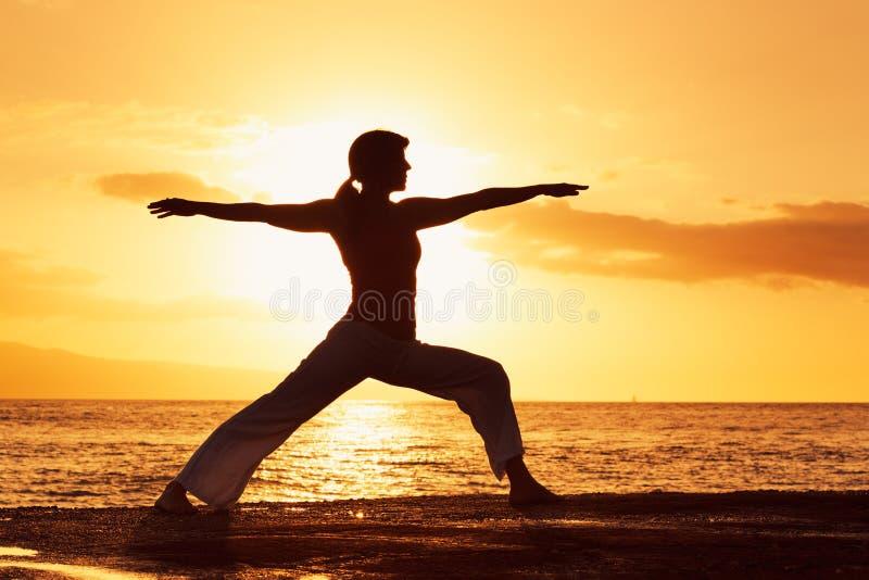 Mujer de la yoga en la puesta del sol fotos de archivo