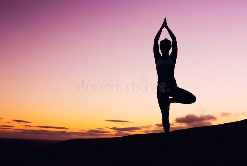 Mujer de la yoga en la puesta del sol imagen de archivo libre de regalías