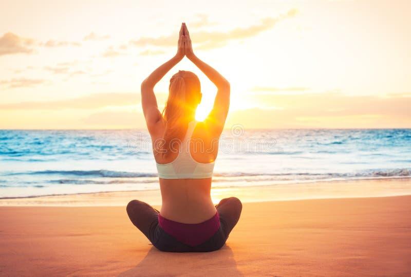 Mujer de la yoga en la puesta del sol foto de archivo