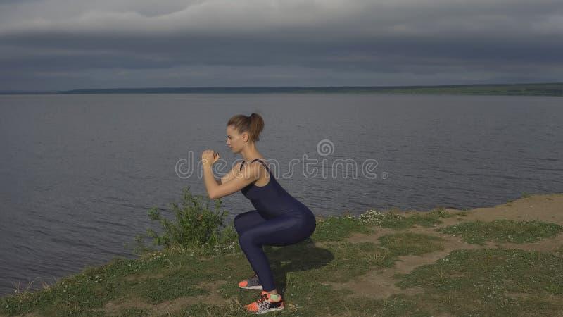 Mujer de la yoga en la ropa de deportes, práctica de la yogui al aire libre imagen de archivo libre de regalías