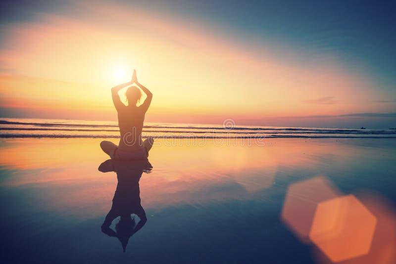 Mujer de la yoga que se sienta en actitud del loto en la playa con la reflexión en agua imágenes de archivo libres de regalías