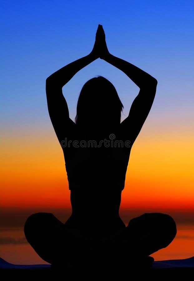 Mujer de la yoga sobre puesta del sol imagenes de archivo