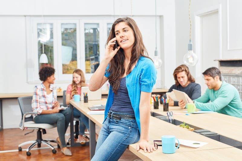 Mujer de lanzamiento joven que llama por teléfono en la reunión foto de archivo