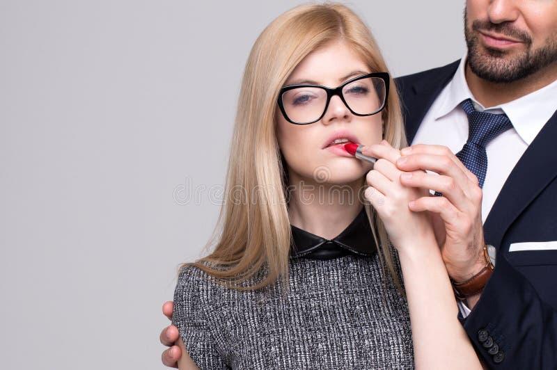 Mujer de las ayudas del hombre que aplica la barra de labios roja imagen de archivo