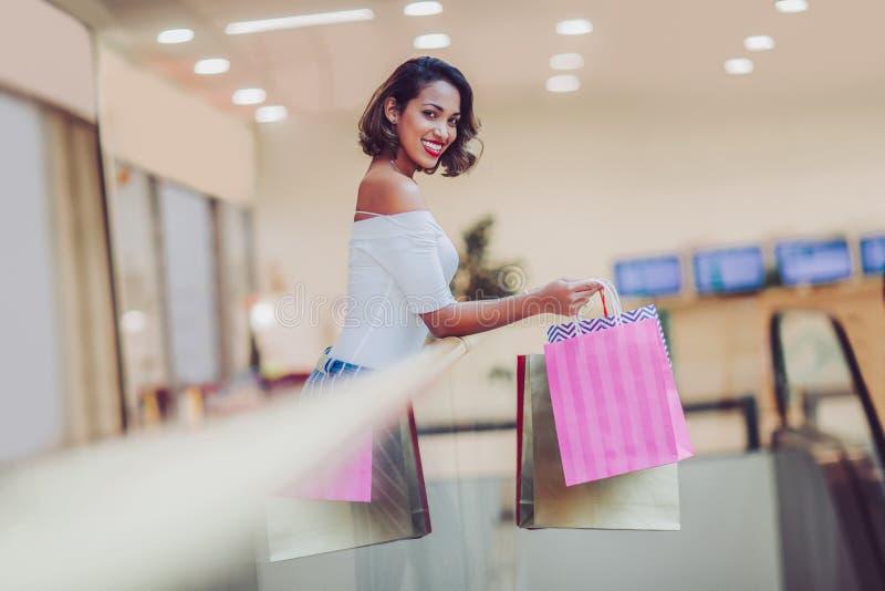 Mujer de las compras que sonríe y que sostiene bolsos en alameda de compras imagen de archivo libre de regalías