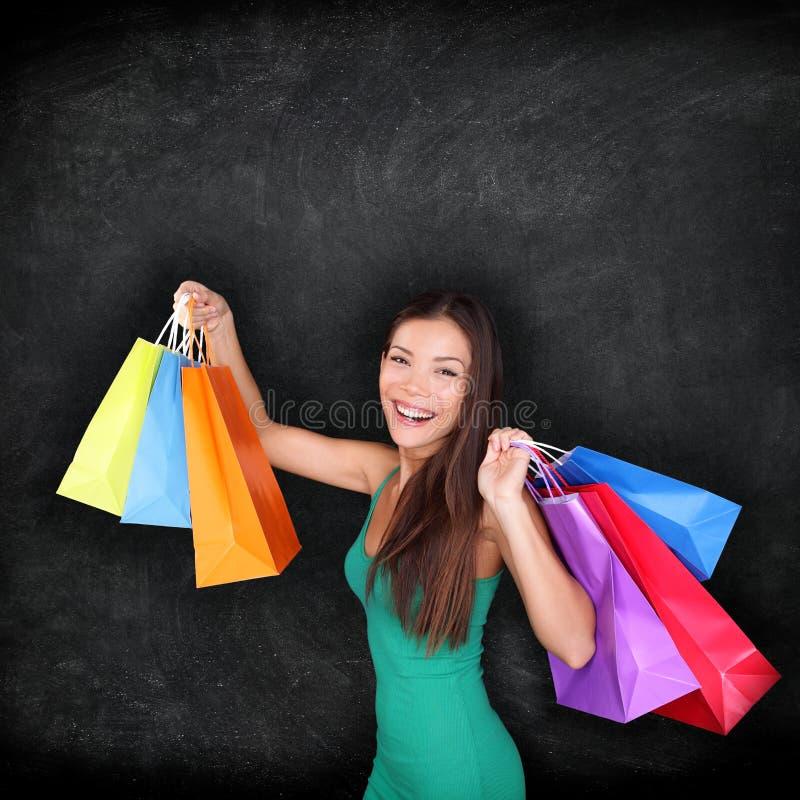 Mujer de las compras que sostiene bolsos de compras en la pizarra imágenes de archivo libres de regalías