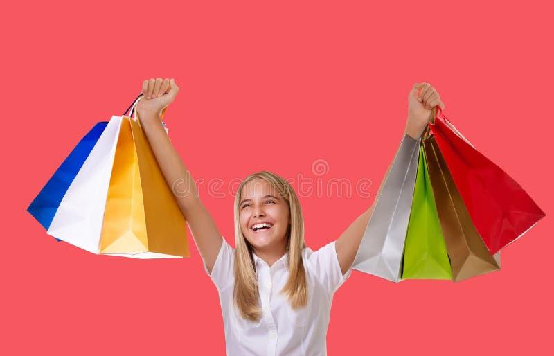 Mujer de las compras que sostiene bolsos que hacen compras sobre su cabeza que sonríe durante compras de la venta sobre fondo cor fotografía de archivo