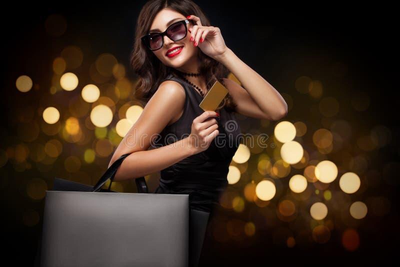 Mujer de las compras que sostiene el bolso gris en fondo del Año Nuevo con el bokeh de las luces en el día de fiesta negro de vie fotografía de archivo