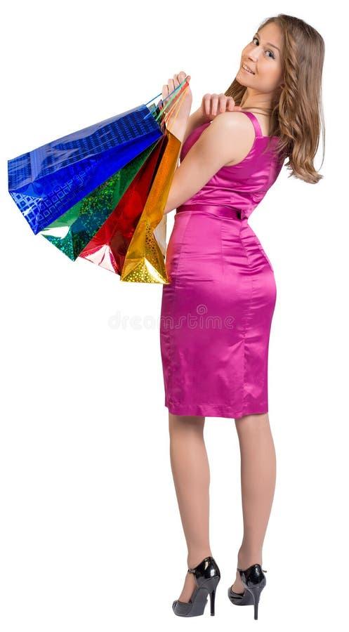 Mujer de las compras que sostiene los bolsos, aislados en blanco fotografía de archivo