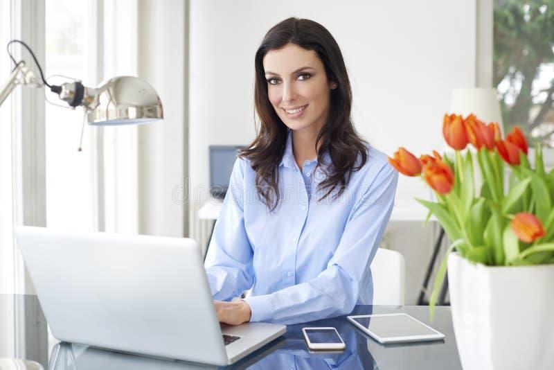 Mujer de las ventas con el ordenador portátil fotos de archivo