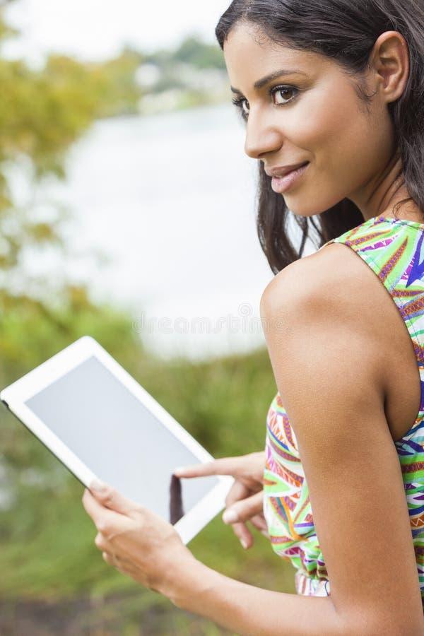 Mujer de Latina de la raza mixta que usa el ordenador de la tablilla foto de archivo