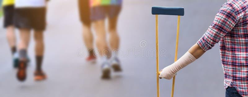 Mujer de lesión con el bandadge que sostiene las muletas de madera en b imágenes de archivo libres de regalías