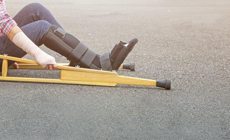 mujer de lesión con la ayuda del brazo de la pierna que lleva quebrada, molde negro de la pierna imágenes de archivo libres de regalías
