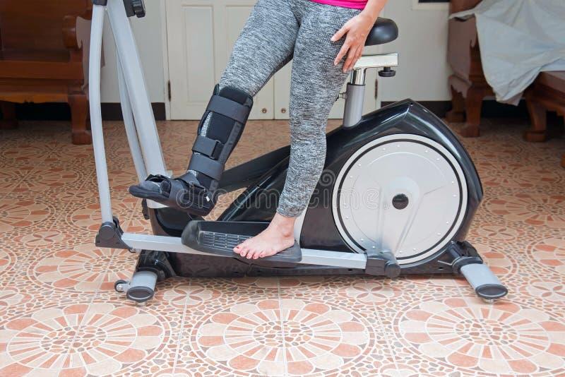 mujer de lesión con la tablilla negra en la pierna que se coloca en la bicicleta estática fotografía de archivo
