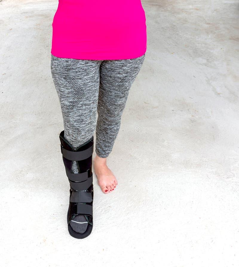 mujer de lesión en ropa de deportes con la tablilla negra en la pierna que coloca o foto de archivo libre de regalías