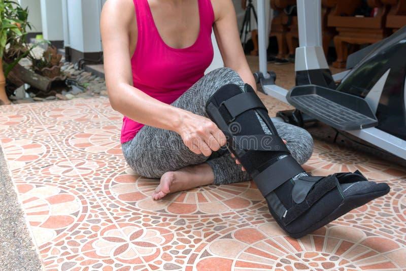 mujer de lesión en ropa de deportes con la tablilla negra en la pierna que se sienta encendido fotos de archivo libres de regalías