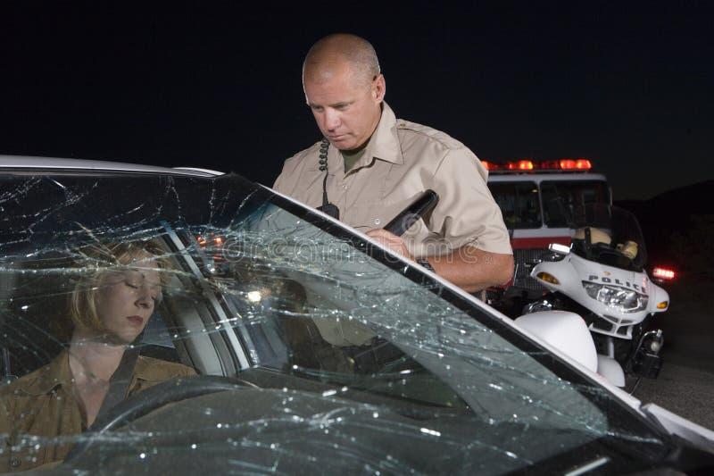 Mujer de Looking At Unconscious del oficial en coche fotos de archivo