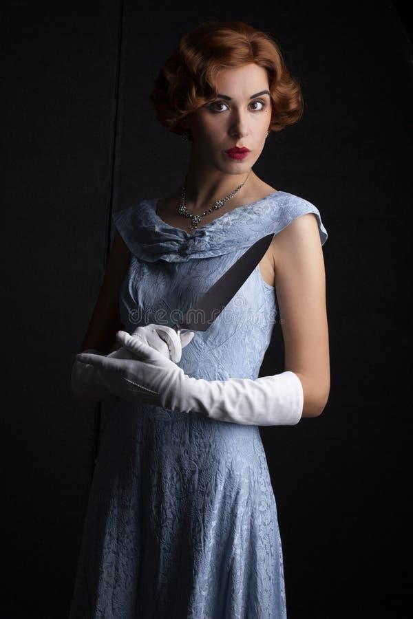 mujer de los años 30 en el vestido azul que sostiene un cuchillo foto de archivo libre de regalías