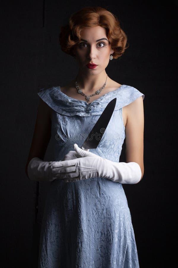 mujer de los años 30 en el vestido azul que sostiene un cuchillo fotos de archivo