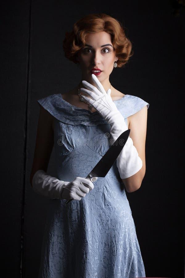 mujer de los años 30 en el vestido azul que sostiene un cuchillo foto de archivo