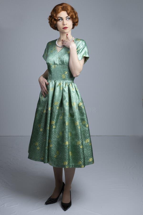 mujer de los años 50 en vestido verde del satén fotos de archivo