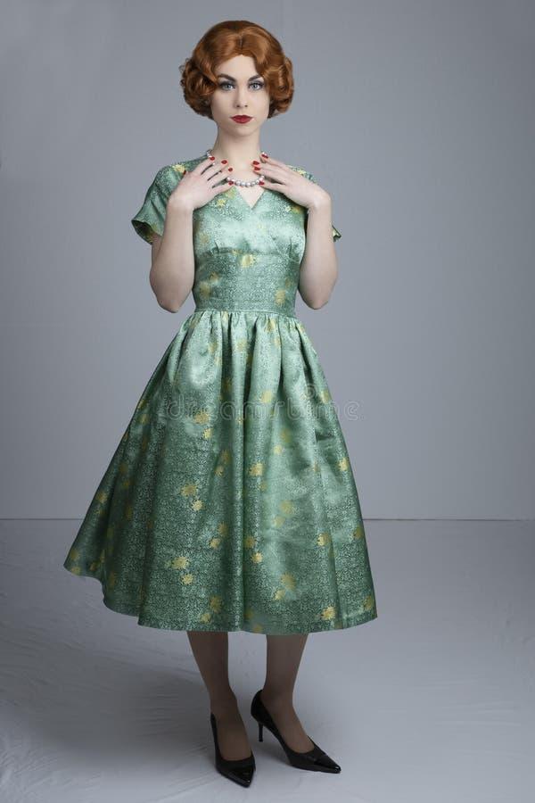 mujer de los años 50 en vestido verde del satén imagenes de archivo