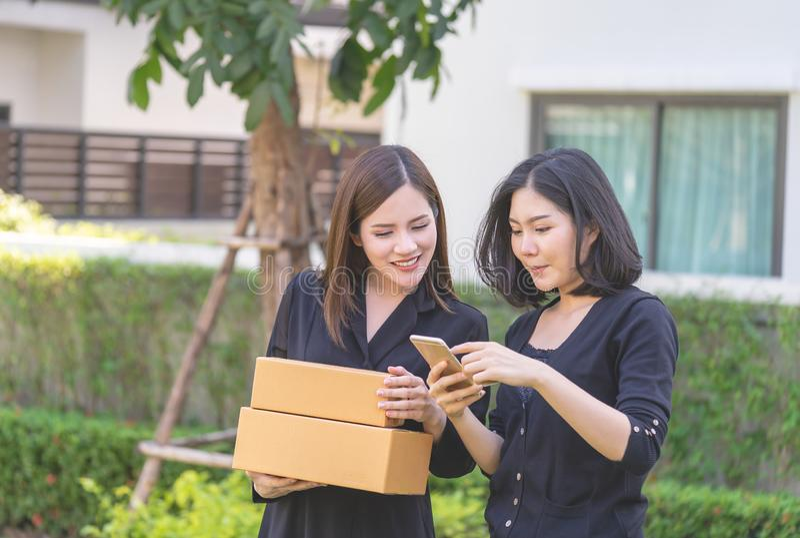 Mujer de los amigos que usa smartphone para hacer compras en línea con la mano ho fotografía de archivo