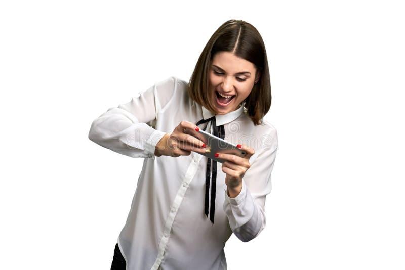 Mujer de los asuntos divertidos que juega en smartphone foto de archivo libre de regalías