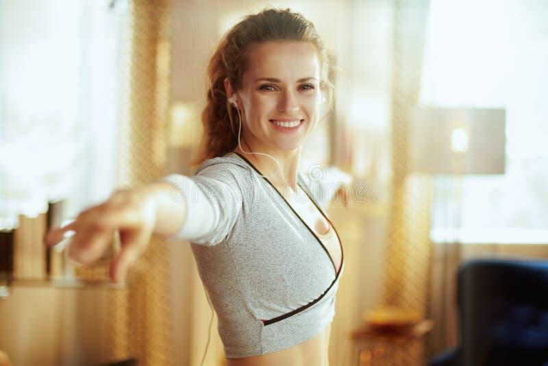 Mujer de los deportes que escucha la música y que hace aptitud de la danza imagen de archivo libre de regalías