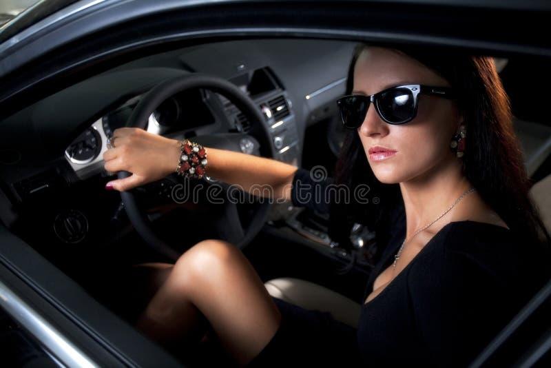Mujer de lujo con las piernas largas que se sientan en el coche foto de archivo