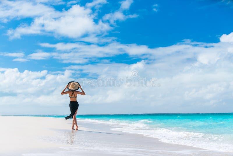 Mujer de lujo de la playa del viaje del verano que camina por el océano imagen de archivo