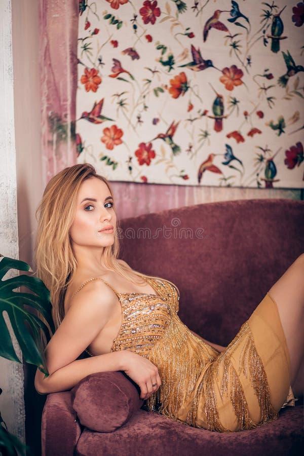Mujer de lujo que sorprende en el vestido de oro elegante que presenta en el sofá imagen de archivo