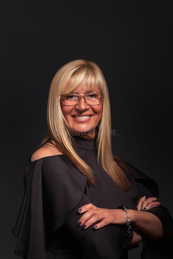 Mujer de mediana edad acertada con el retrato de los vidrios foto de archivo