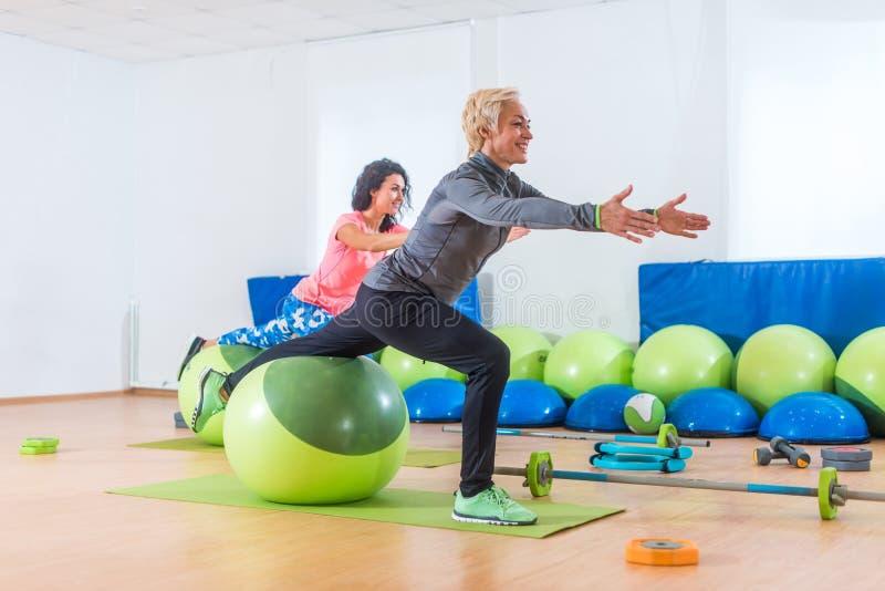 Mujer de mediana edad activa que se resuelve con la bola de la estabilidad que participa en clase de la aptitud del grupo fotografía de archivo