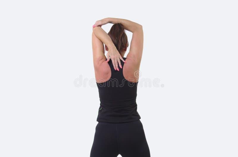 Mujer de mediana edad atractiva en engranaje de los deportes que calienta con estiramiento del hombro imágenes de archivo libres de regalías