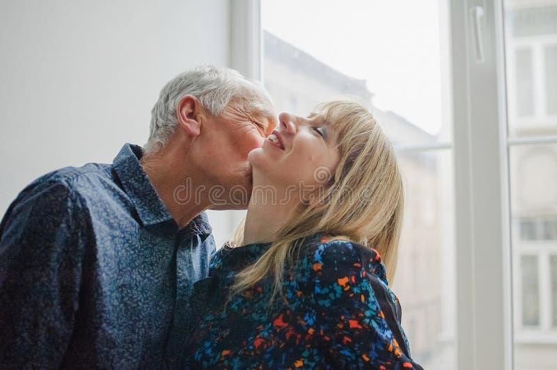 Mujer de mediana edad caliente y atractiva que disfruta de besarse de su marido mayor que se coloca cerca de ventana abierta dent imagenes de archivo