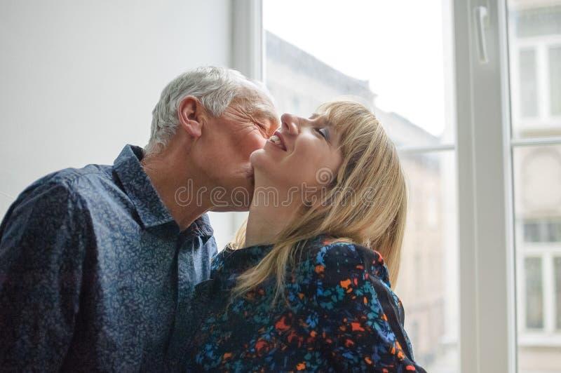 Mujer de mediana edad caliente y atractiva que disfruta del abrazo de su marido mayor que se coloca cerca de ventana abierta dent fotografía de archivo libre de regalías