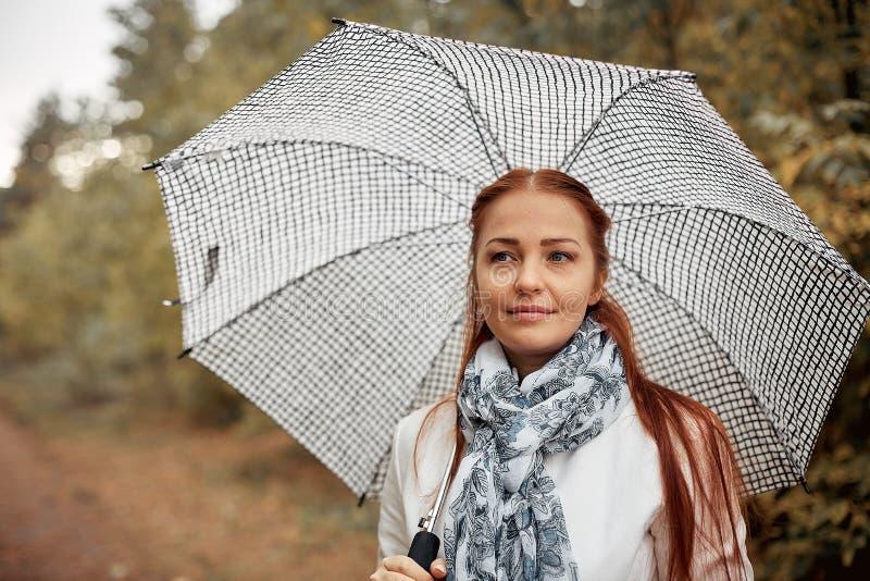 Mujer de mediana edad caucásica hermosa con el pelo rojo con un paraguas en el parque en un día nublado del otoño foto de archivo