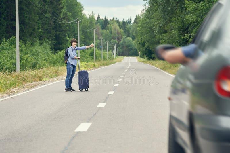 Mujer de mediana edad con un bolso del viaje que hace autostop en el camino rural en verano imagenes de archivo