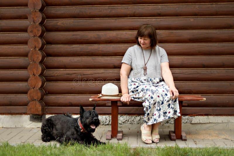 Mujer de mediana edad en un campo que se sienta en un banco de madera y que mira un schnauzer negro cerca de una cabaña de madera imagen de archivo